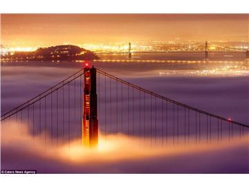 夕阳余晖下大雾涌入金门大桥 宛如来自天堂聚光灯